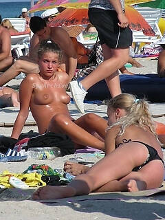 Voyeur footage of some hot naked women hanging out on the beach
